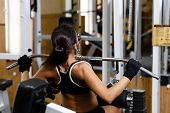 stock photo of lats  - Sports young woman doing exercises in the gym on Lat Machine - JPG