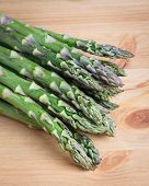 stock photo of spears  - Bunch of fresh green asparagus spears on a rustic wooden table - JPG