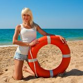 stock photo of lifeline  - Beautiful slim girl on the beach with a lifeline - JPG