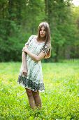 stock photo of beatitudes  - Girl stands in the middle of a lawn with flowers - JPG
