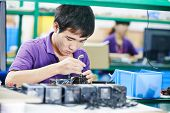 stock photo of assembly line  - one chinese worker assembling production at line conveyor in china factory - JPG