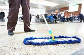 stock photo of broom  - cleaner with mop and uniform cleaning hall floor of public business building - JPG