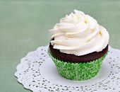 stock photo of icing  - A cute chocolate cupcake with vanilla icing and copy space - JPG