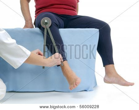 Physiotherapist measuring active range of motion of older patient's lower limb using manual goniometer