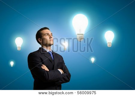 Image of confident businessman with arms crossed looking at bulb. Idea concept