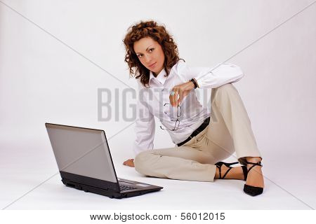 A young girl with a lap top at home on the floor