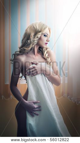 Young blonde woman wrapped in white towel posing relaxed. Beautiful young woman with a towel around