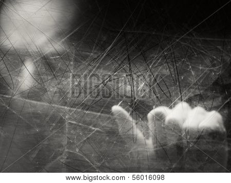 Spooky blurry human face behind dusty scratched glass