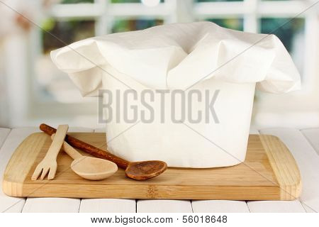 Chef's hat with spoons on board on wooden table on window background