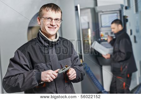 manufacture technician workers measuring detail and working on metal machining center at factory