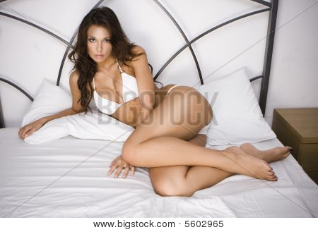 Young Brunette Woman On The Bed