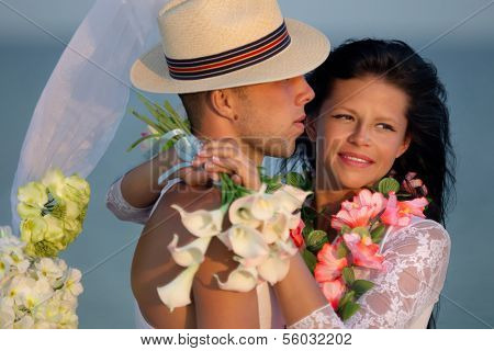 Groom with bride wearing lei, under archway on beach