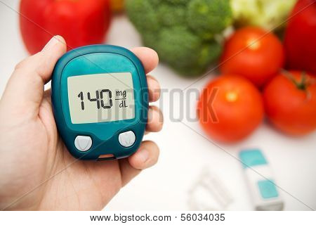 Diabetes doing glucose level test. Vegetables in background