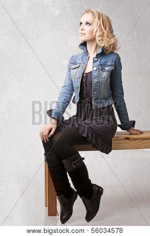 portrait of a young beautiful woman with loose curly hair blond hair wearing blue jean jacket with retro effect sitting on the bench