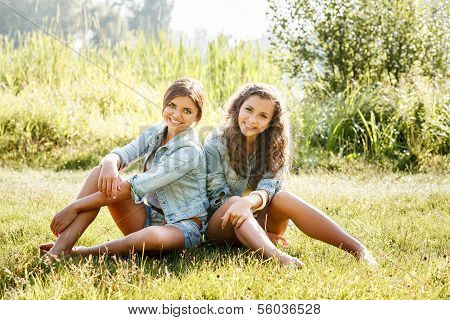 Two Girlfriends Sitting On Grass