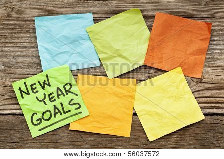 New Year goals - handwriting on a sticky note against grained wood with blank notes