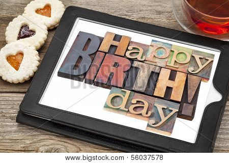 Happy birthday in letterpress wood type on digital tablet with stylus a cup of teat and heart cookies