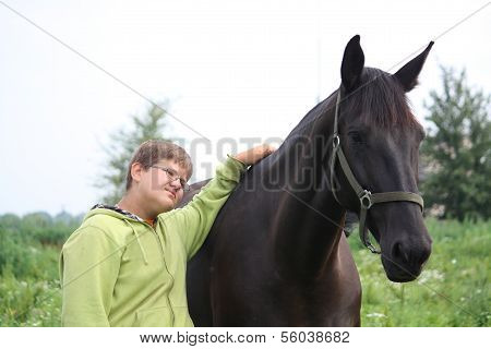 Smiling Teenager Boy With Horses At The Field