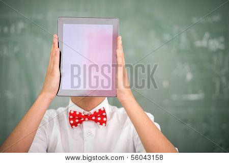 Student with bowtie holding tablet in front of his head