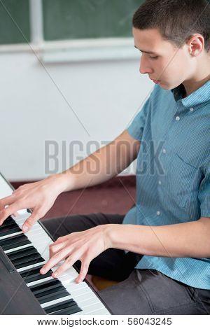 Highschool niño tocando el piano en el aula