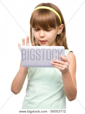 Young nearsighted girl is using tablet, isolated over white