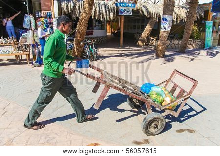 DAHAB, EGYPT - JANUARY 24, 2011: Man pushing cart down the street on January 24, 2011 in Dahab, Egypt. This method of transporting goods is common in Egypt.