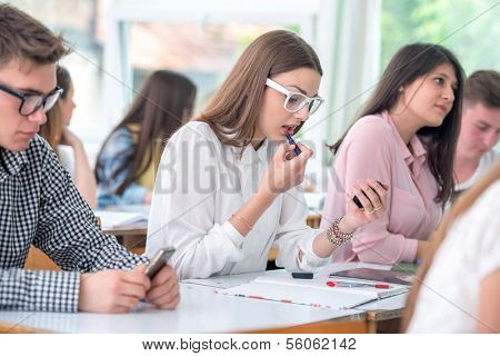 Handsome highschool girl putting lipstick in classroom