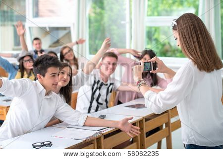 Highschool girl taking a picture of classroom with mobile phone