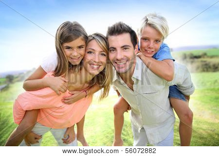 Parents giving piggyback ride to kids