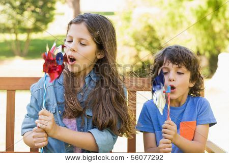 Cute young boy and girl blowing pinwheels on park bench