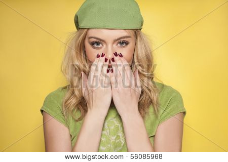 Beautiful woman with long blond hair wearing a chic green outfit showing off her manicured nails on a yellow background