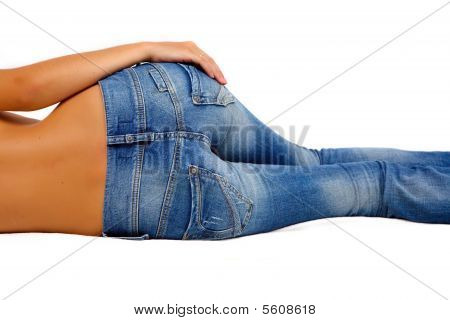 Topless girl in blue jeans laying on the floor