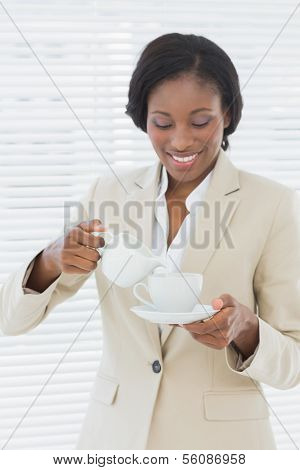 Portrait of an elegant young smiling businesswoman with a cup of tea in the office