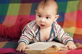 pic of new years baby  - cute baby reading book on colorful background