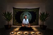 stock photo of magickal  - A man sitting on a zafu with in a white robe staring intensely into the camera with his eyes open doing a meditation ritual. There are plants candles and a tapestry behind him on the wall.