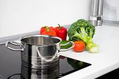 Pot And Vegetables In Modern Kitchen With Induction Stove