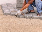 stock photo of masonic  - mason worker making pavement with stone blocks - JPG