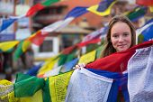 Teen-girl in Buddhist monastery, with Buddhist prayer flags flying.