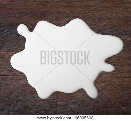 White milk drop on wooden background.