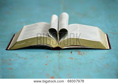 Heart formed by open Bible on vintage table