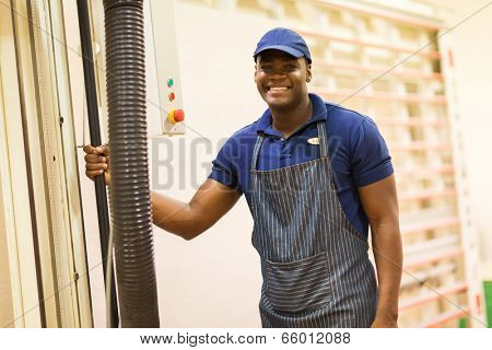 african male hardware store worker standing next to wood board cutting machine