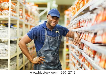 smiling african hardware store worker standing by the fasteners aisle