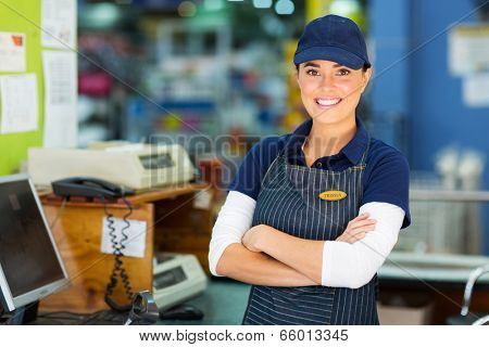 happy female hardware store cashier with arms folded