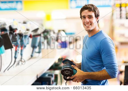 smiling young man purchasing a hand tool in hardware shop