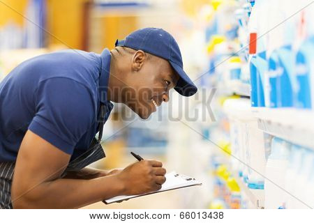 cheerful african hardware store worker taking stock
