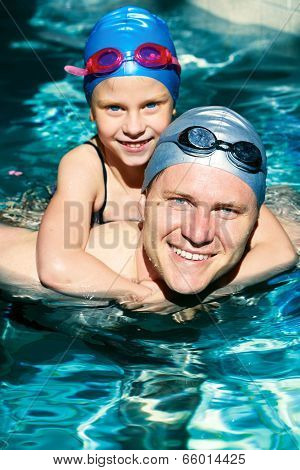 Young Father With Little Daughter Swimming In Pool