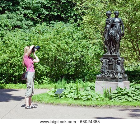 The young woman photographs sculptures in palace park of Lomonosov. Petersburg. Russia.