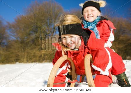 Sisters in snow on toboggan