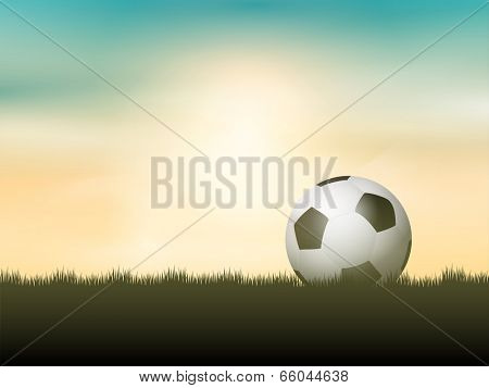 Soccer ball or football nestled in grass against a sunset sky