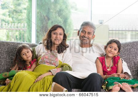 Indian family at home. Asian parents and children living lifestyle, sitting on couch indoor smiling happily.